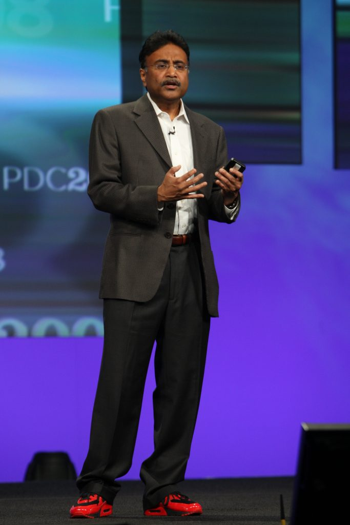 "Amitabh Srivastava on stage at PDC 2008, wearing the ""Project Red Dog"" sneakers that Dave Cutler helped design."