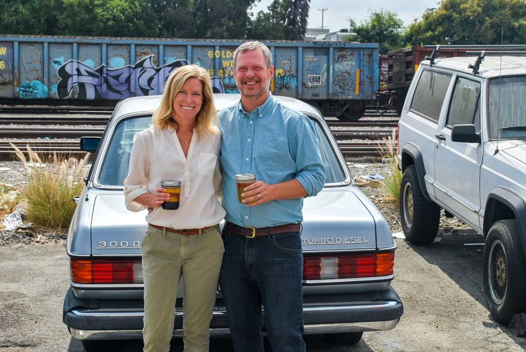 Megan and Marshall Dostal hold jars of grease in front of Marshall's Mercedes 300D