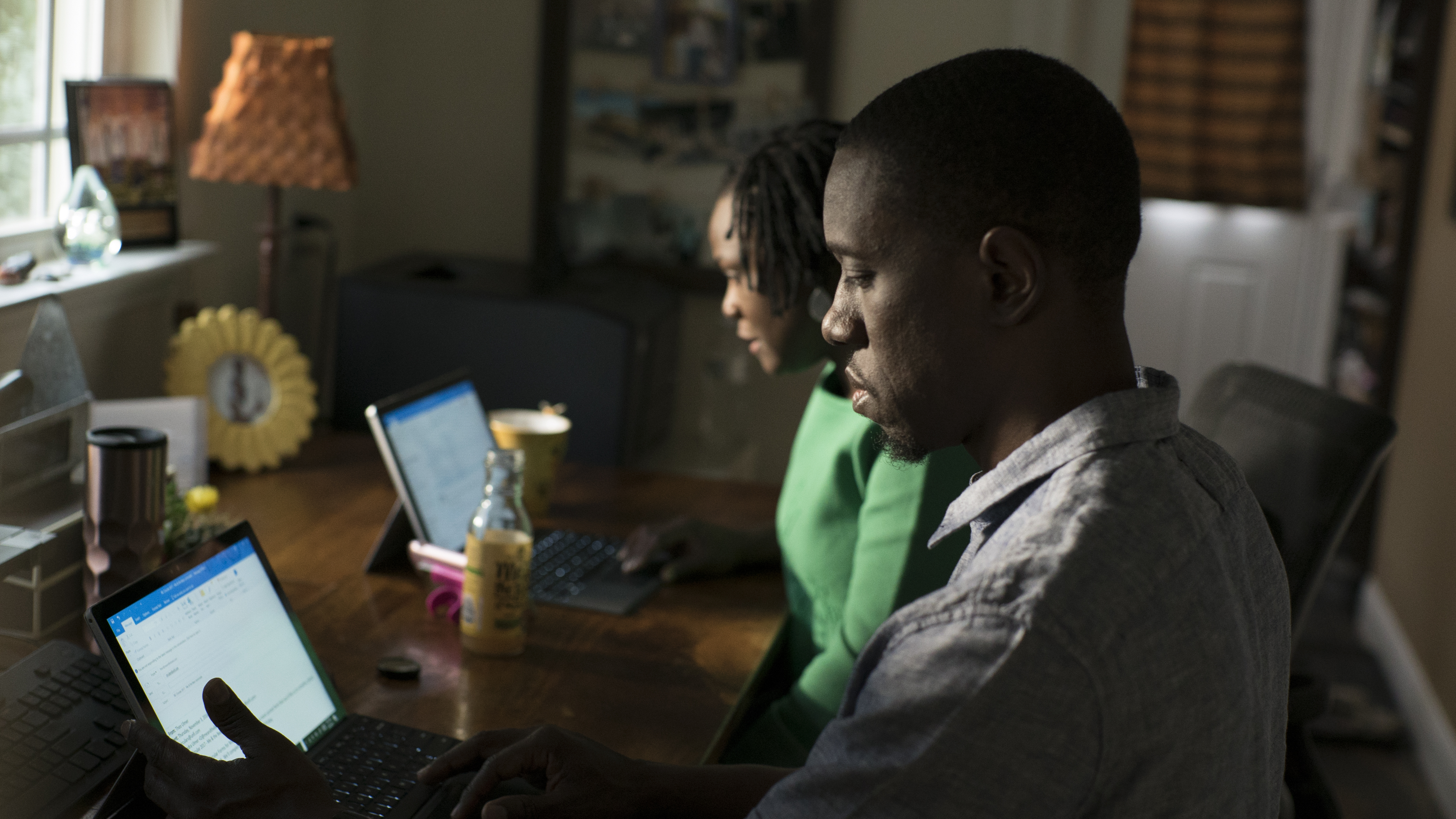 Photo of man and woman working side by side on laptops.