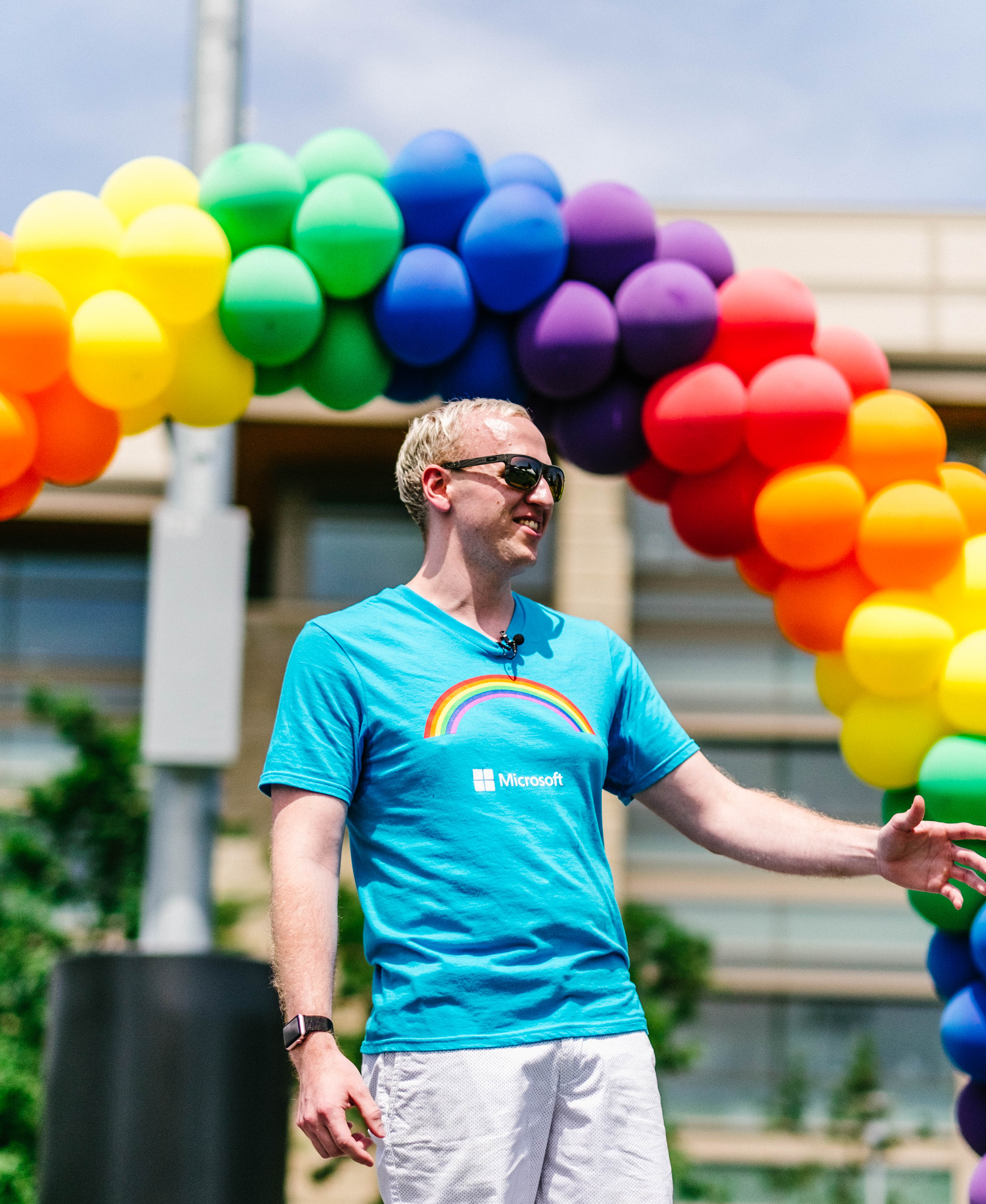 Photo of man with rainbow of balloons in background
