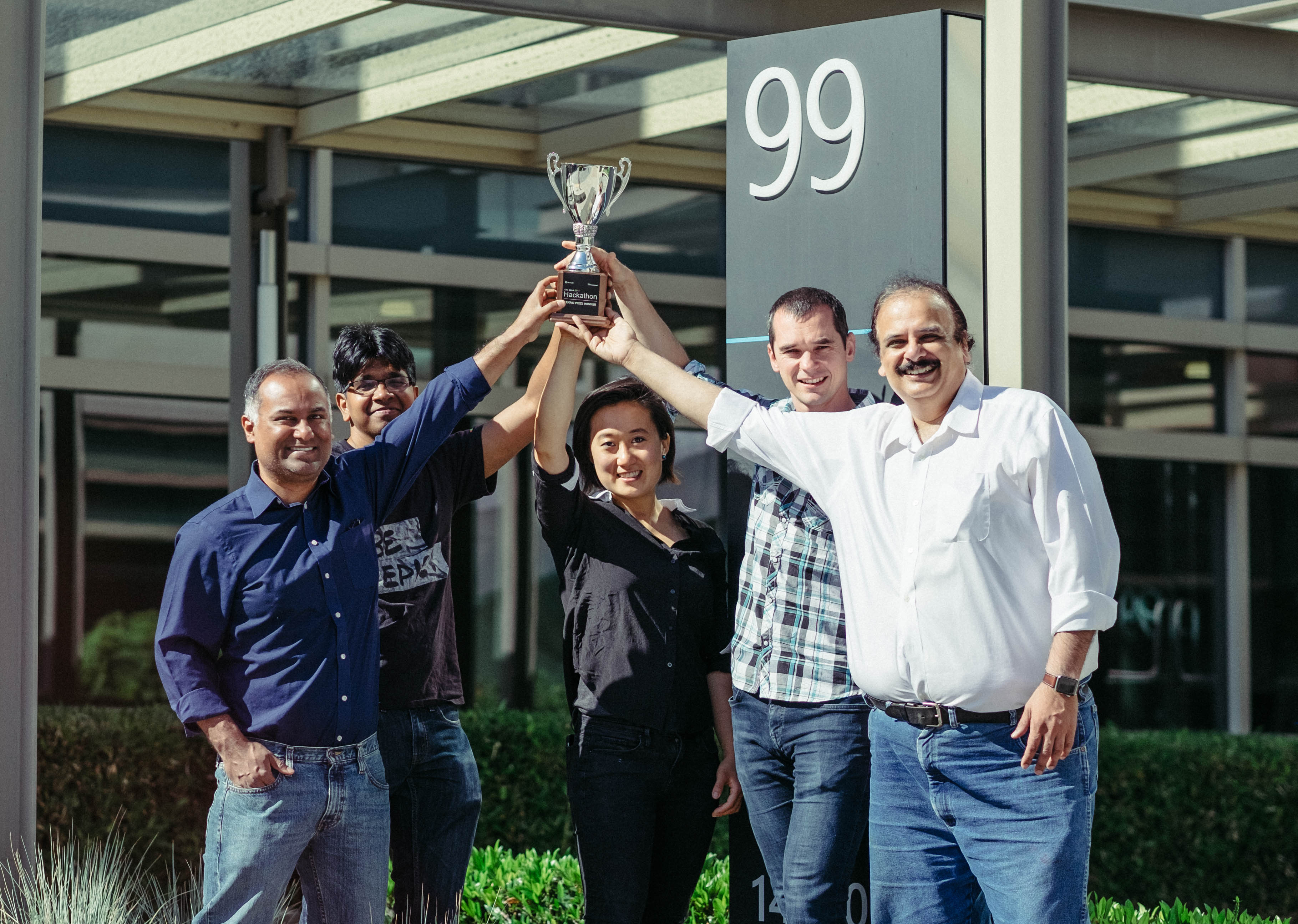 The five members of the winning Hackathon 2017 team (four men and one woman) stand in a semi-circle holding the trophy aloft.