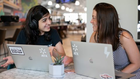 Two women work together behind laptops