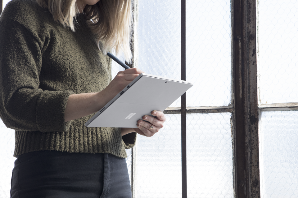 Woman standing up by window using Microsoft Surface device and Pen