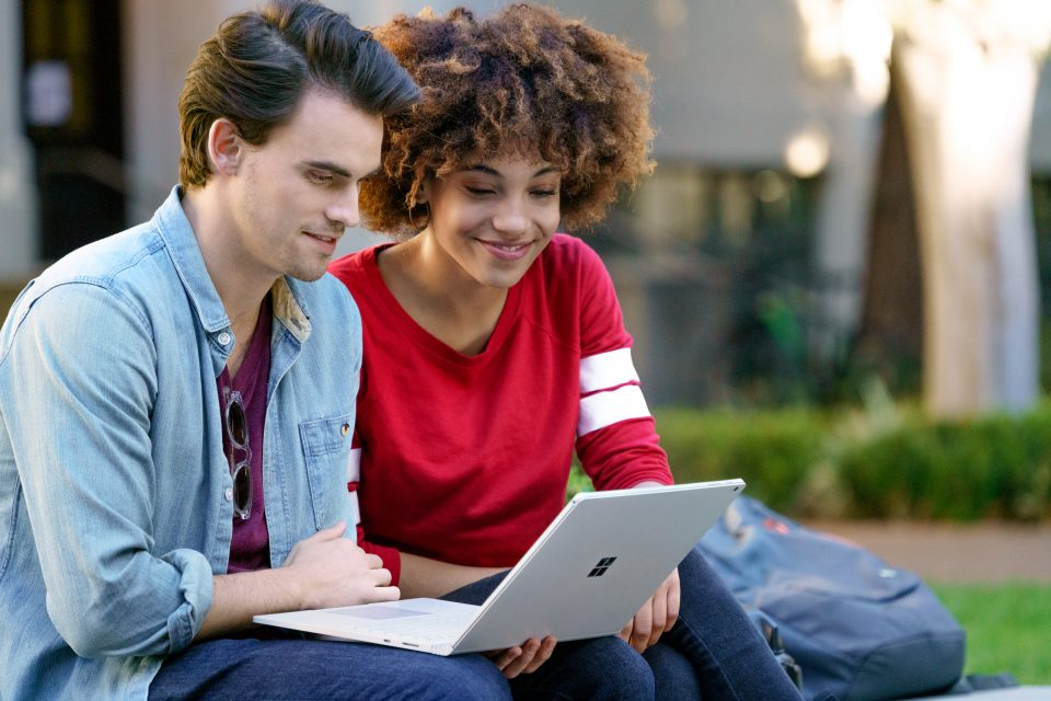 Teenage boy and girl sitting outside at university looking at Surface Book