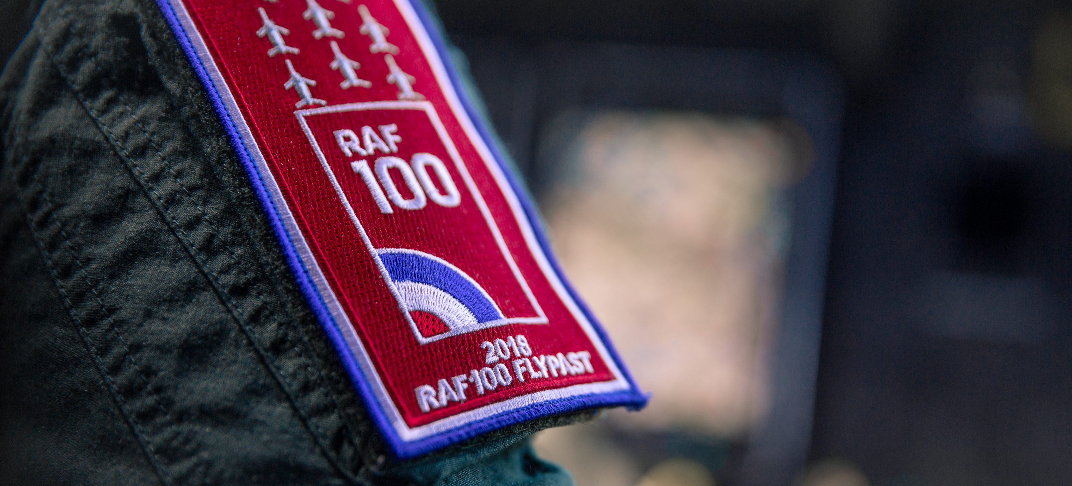 RAF 100 badge on the sleeve of an RAF helicopter pilot about to take part in the Centenary Flypast over Buckingham Palace in London