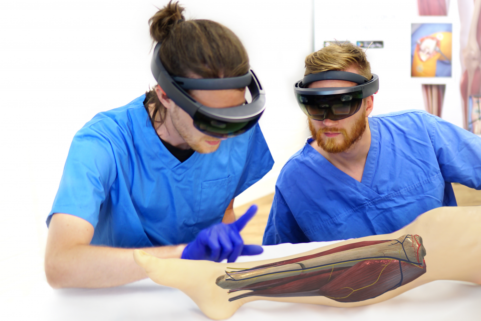 Two surgeons using HoloLens to look at leg during operation