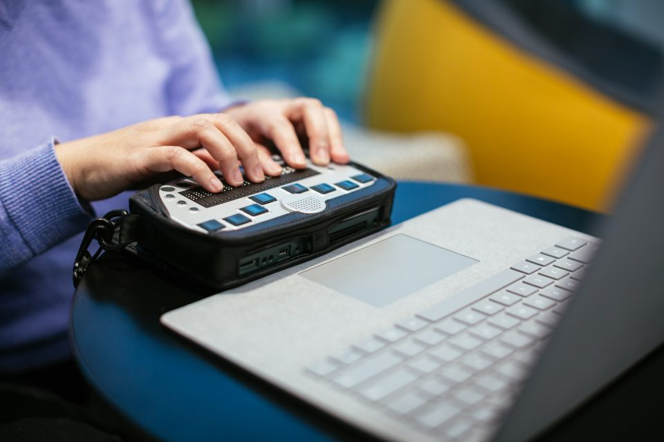 A woman types on a braille keyboard while using a Surface Book