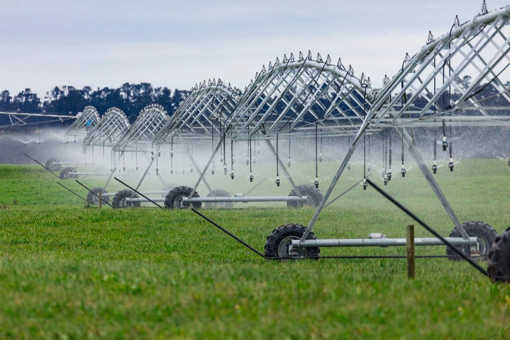Large irrigation equipment sprays water on green field