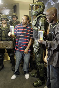 "Hip-hop artist Ludacris (center) is on hand to celebrate the launch of ""Halo 3"" for Xbox 360 with the game's hero, Master Chief, and Darnell Jefferson (right) one of the first recipients to receive the game at midnight in New York, Sept. 25."