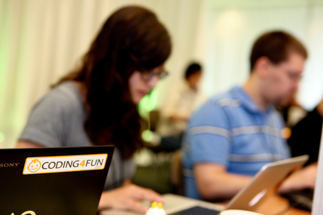 "A Code Camper's laptop sports the sticker ""CODING 4 FUN"" while developers Shani Jayant and Josh Blake are in the background doing the same during Code Camp on Wednesday on Microsoft's Redmond Campus. Redmond, Wash."