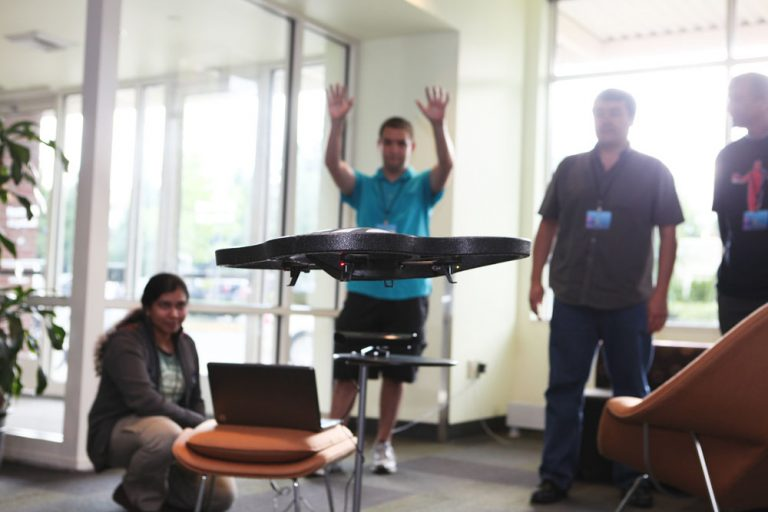 Student Alex Wiggins gestures to Kinect, which in turn makes a remote-control toy helicopter take off while teammates Ruma Paul (left) and Fabio Matsui (right) look on. The trio was one of 50 people participating in Code Camp on Wednesday on Microsoft's Redmond Campus.