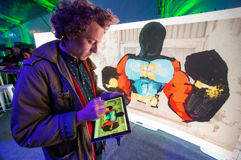 Anthony Lister projecting art to LED from Surface Pro 3 at Windows 10 fan celebration in Sydney, Australia.