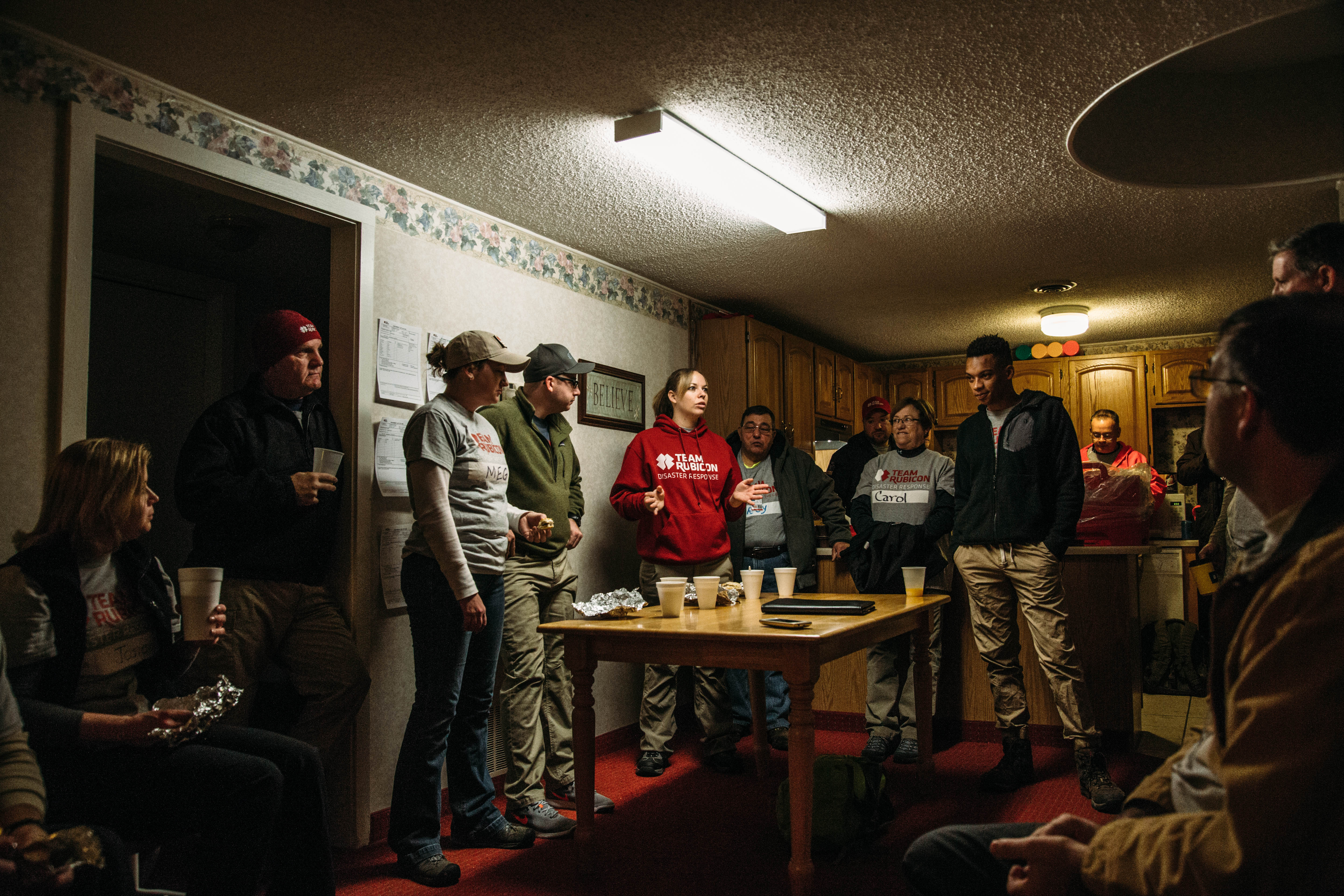 Photo of a group of volunteers standing and talking in someone's home