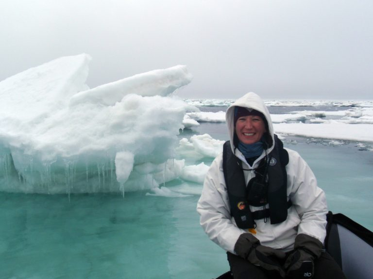 Woman sits on boat with iceberg behind her