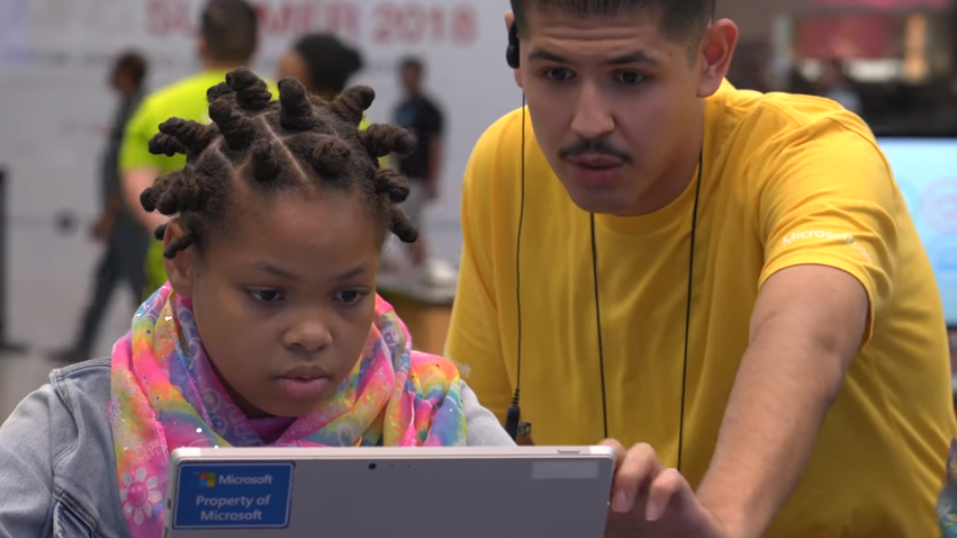 A man and a little girl view a laptop