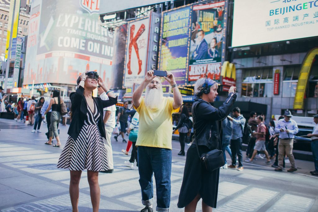 Three people standing in Times Square, one with a Microsoft HoloLens and two with smartphones