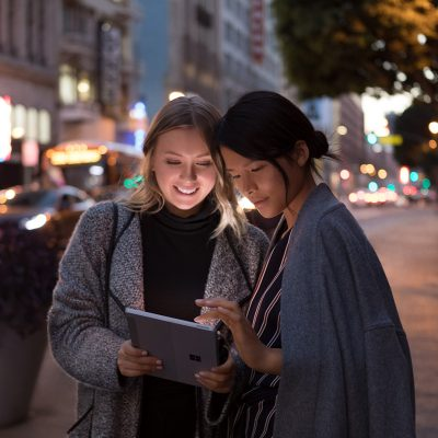 Two women use Surface Go on a dark street