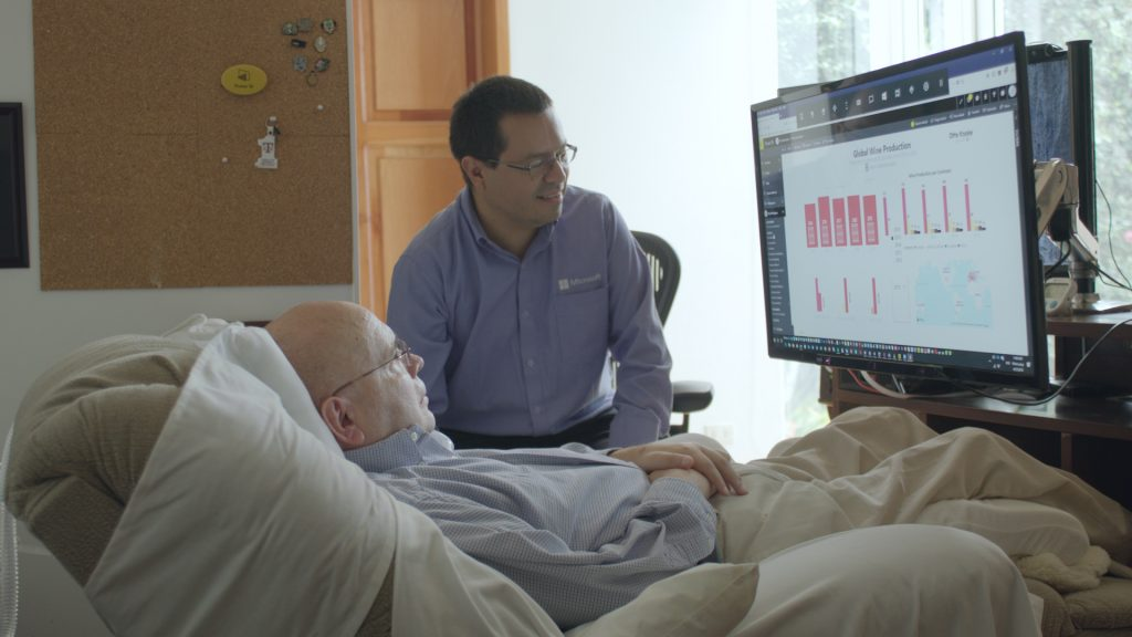 One man lies in a bed and another sits at his side, both looking at a computer screen