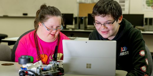 Image of a teenage girl and boy sitting looking at a computer as they design their robot.