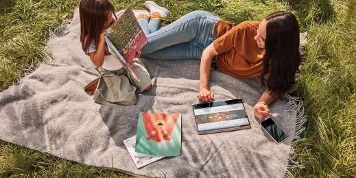 a mother and daughter use devices on a blanket