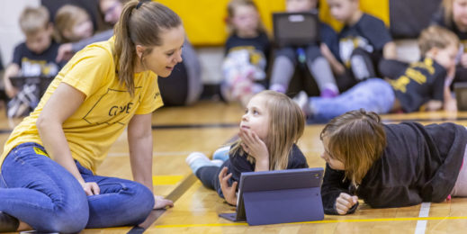 A young woman sits with two children as they use a tablet in a school gymnasium.