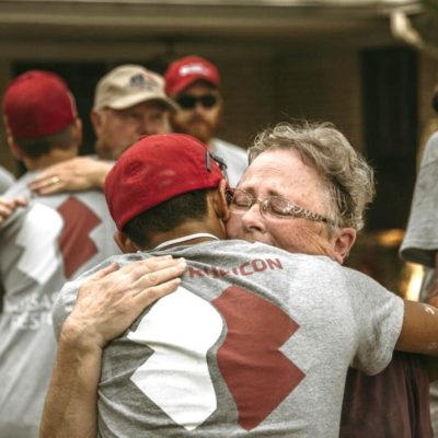 A young man wearing a Team Rubicon tshirt, hugs an older man.