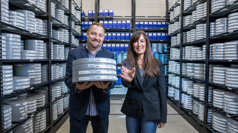 Brad Collar, Warner Bros. senior vice president of global archives and media engineering, left, and Vicky Colf, Warner Bros. chief technology officer, demonstrate the contrast between storing films on 22 reels of film versus a coaster-sized piece of glass