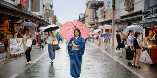 A woman wearing traditional Japanese clothing stands on a city street in Japan holding an umbrella