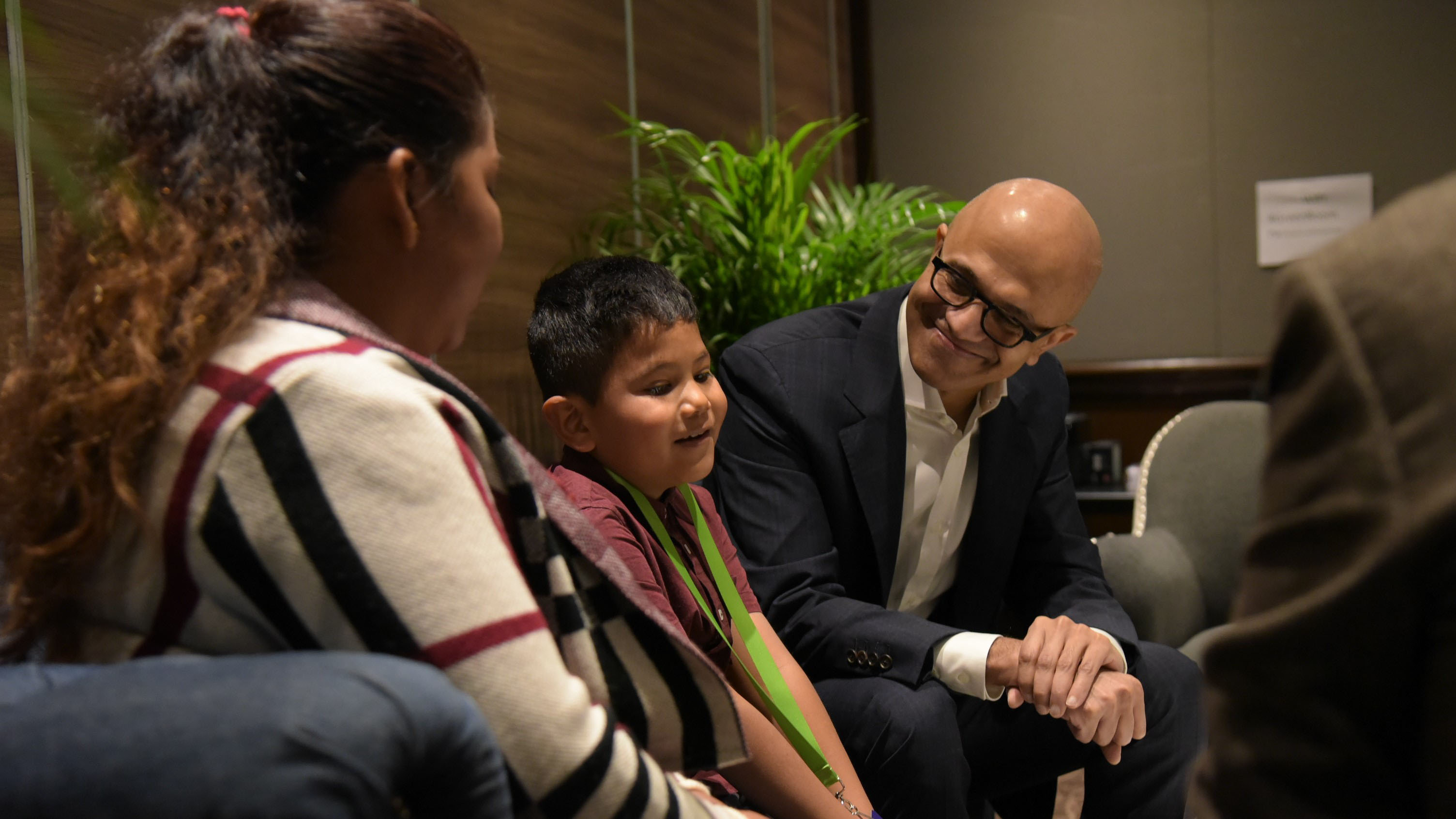 A boy sits next to Microsoft CEO Satya Nadella, who is listening to him talk and smiling