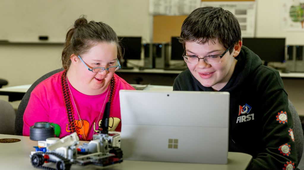 A girl who has Down syndrome and her brother both grin as they look at a computer screen as they plan building a robot