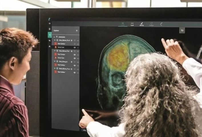 Medical personnel reviewing a scan of a skull