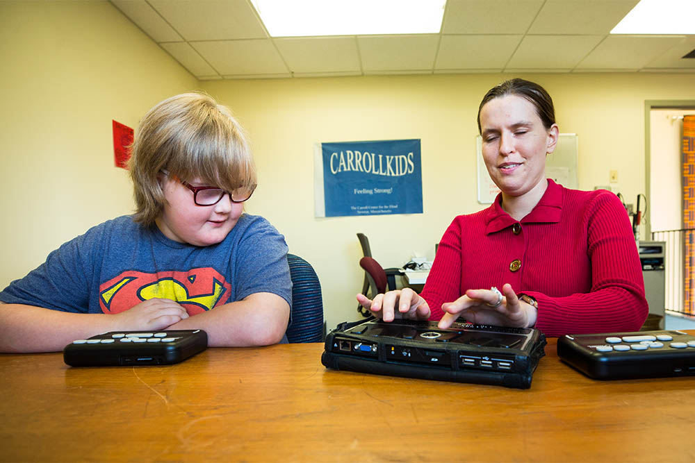 A vision rehabilitation therapist works with an 11-year-old boy on Braille devices
