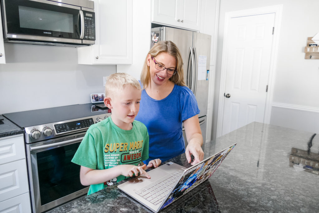Sarah Kimmel in the kitchen working with her son on an open laptop