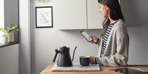 Woman interacts with Microsoft 365 on a phone in her kitchen