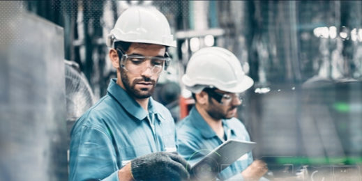 Two men in a factory wearing safety gear and interacting with mobile devices