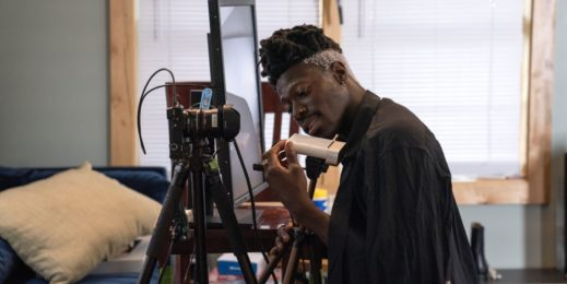 Musician Moses Sumney kneels to examine the Azure Kinect hardware, whi ch is on a tripod next to a mounted camera and a table with a large computer monitor. A blue sofa is in the background; we are in his living room