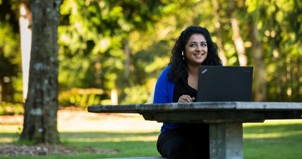 Woman smiles while working on her laptop near trees and grass