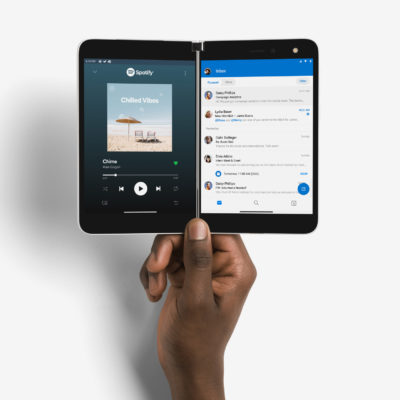 Hand holding Surface Duo displaying Spotify and Outlook