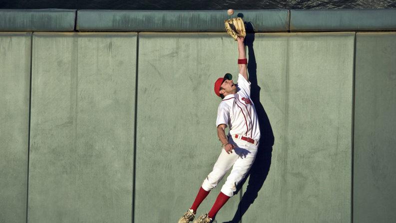 A baseball player jumps to catch a ball