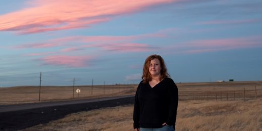 Woman stands near an open field against a blue orange sky during sunset