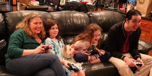 Family of four playing video games together on their couch