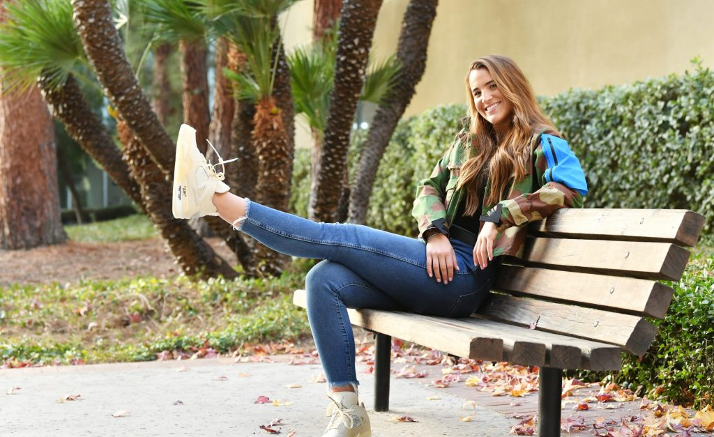 Sabrina Ionescu on a bench with one leg outstretched