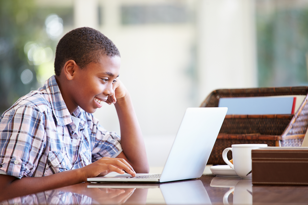 Young primary school boy participating in an online classroom session via his laptop.