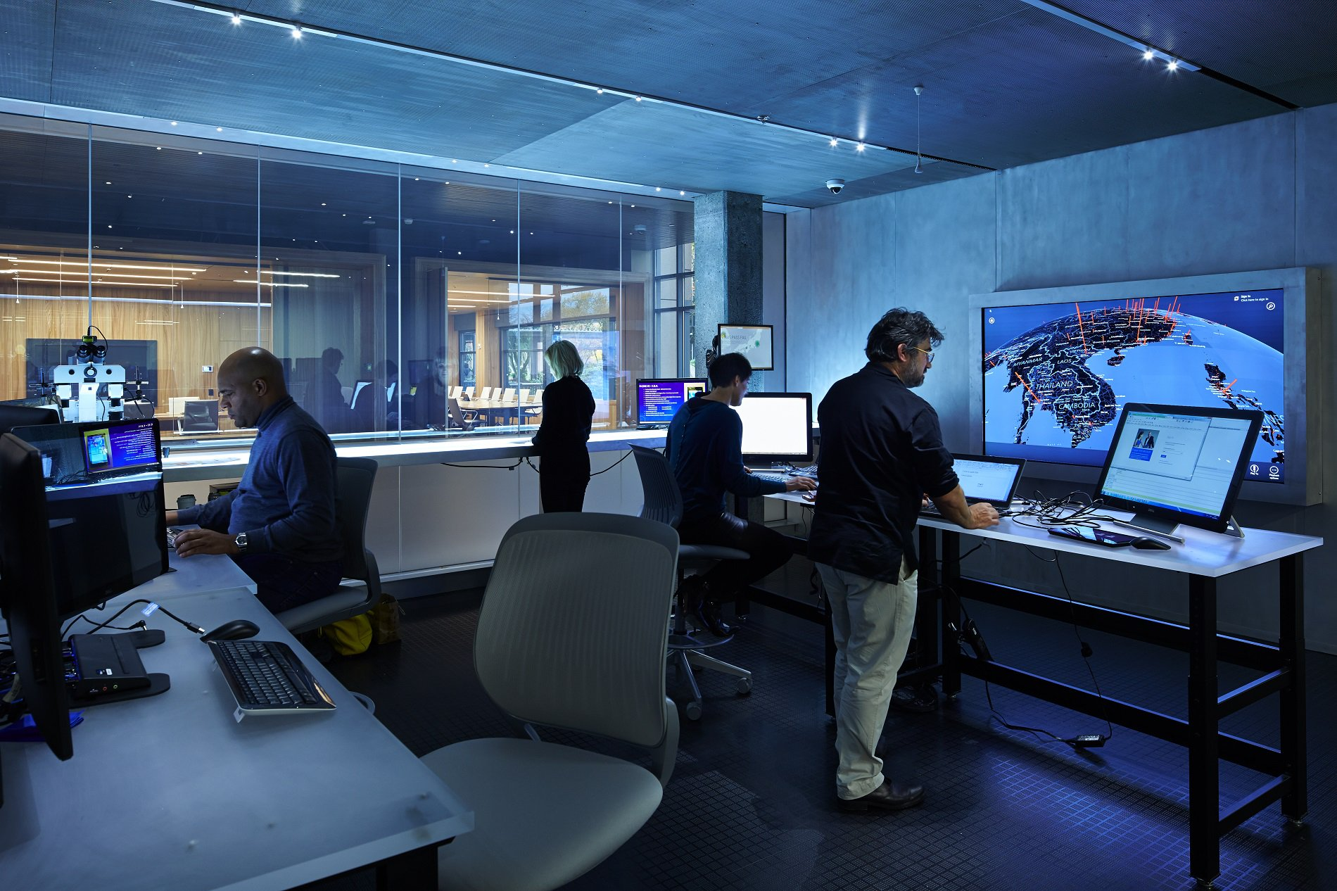Photo of people working in front of computer screens with maps of the world
