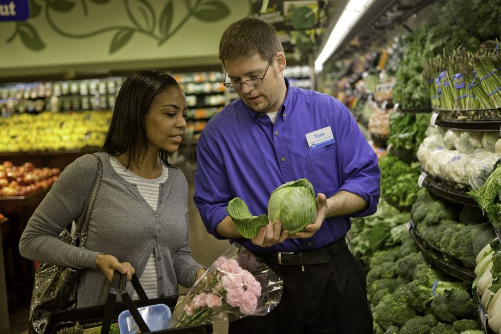 A Kroger customer and associate look at lettucs in the produce section.
