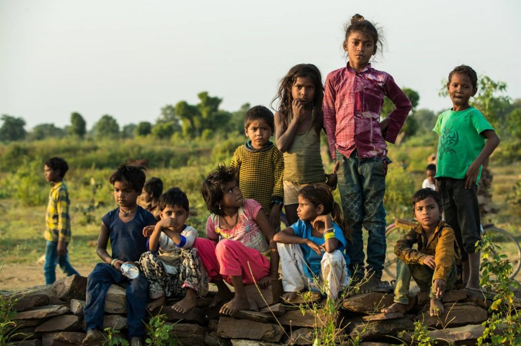 A group of kids, some standing, some sitting, outside in rural India.