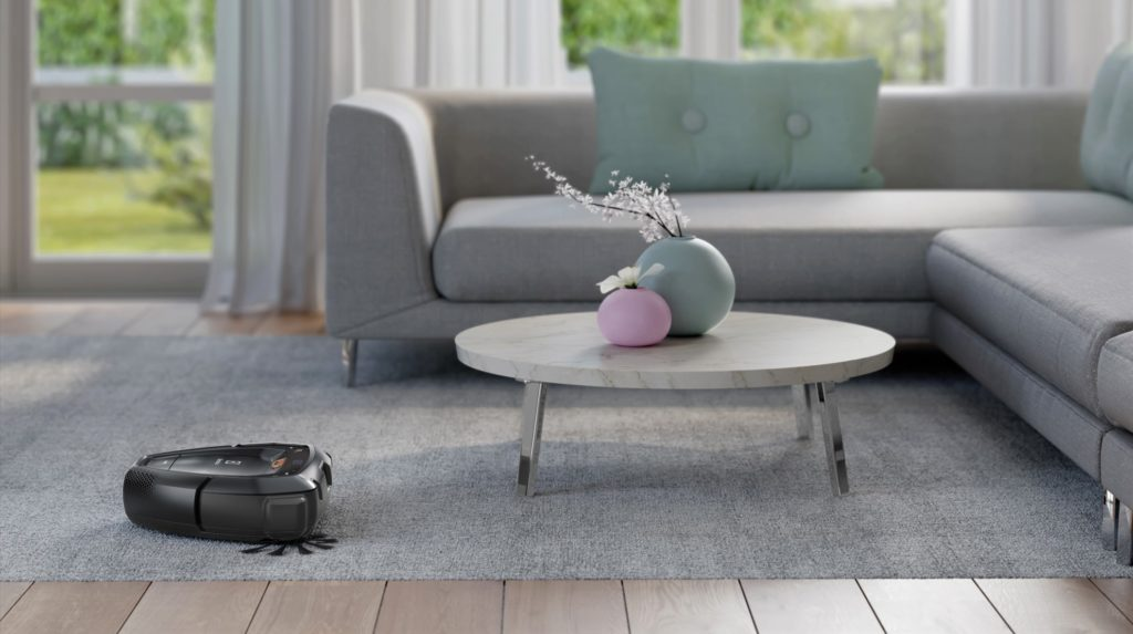 A Pure i9 robotic vacuum moves across a run toward a table and sofa.