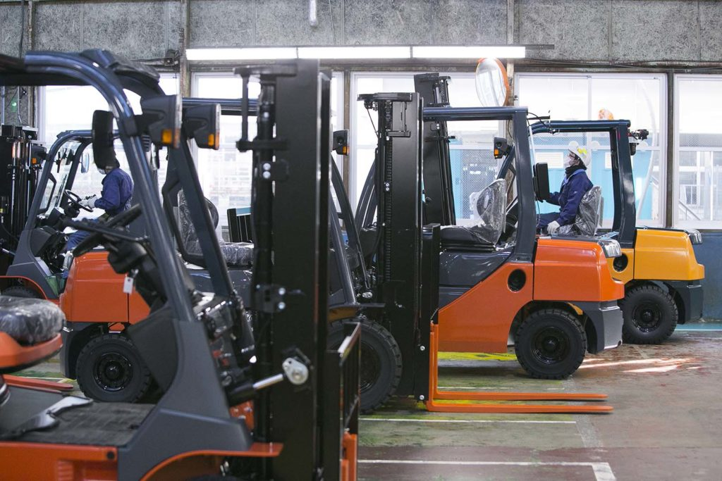 Workers ride forklifts in a warehouse.
