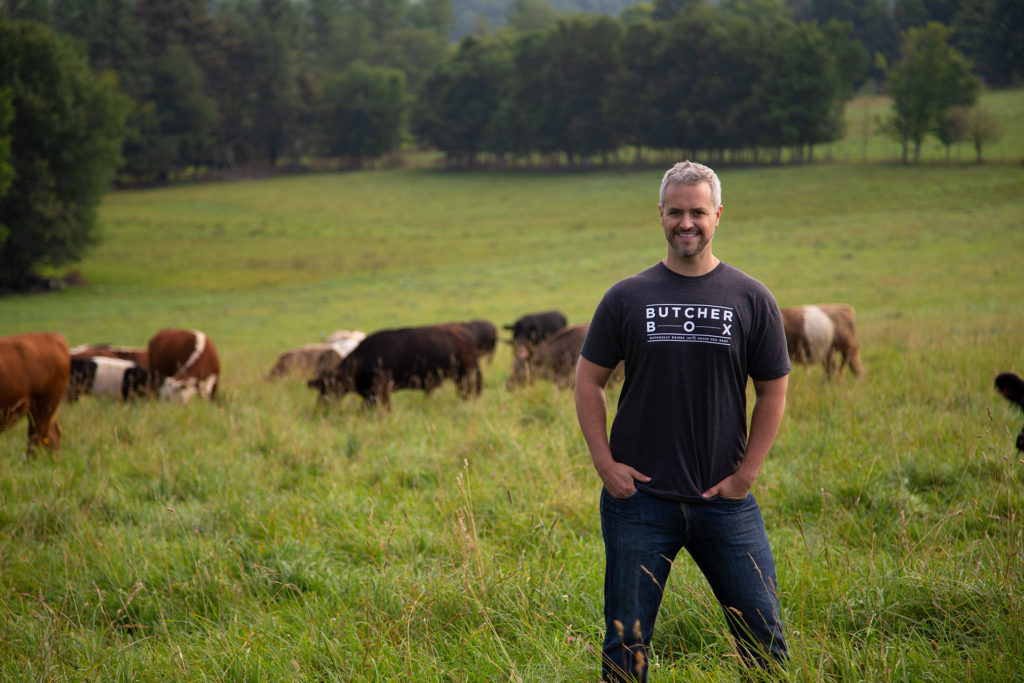 Image of Mike Salguero, the founder and CEO of ButcherBox, standing in a field with cows in background