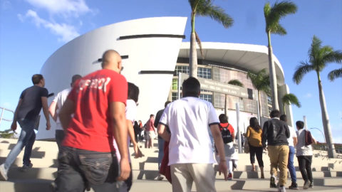 Fans walk into AmericanAirlines Arena in Miami to attend a Miami Heat game.